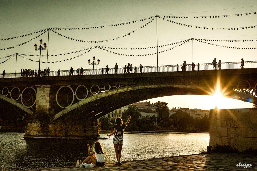 Niñas bailando mirando el puente de triana, Sevill. foto: digodugo